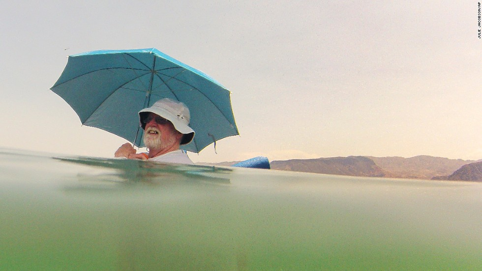 Mike Bouse shades himself with an umbrella as he floats in the water at Lake Mead near Boulder City, Nevada, on Saturday, June 29.