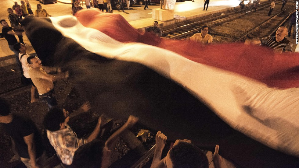Morsy opponents wave a giant national flag outside the presidential palace on Saturday, June 29.