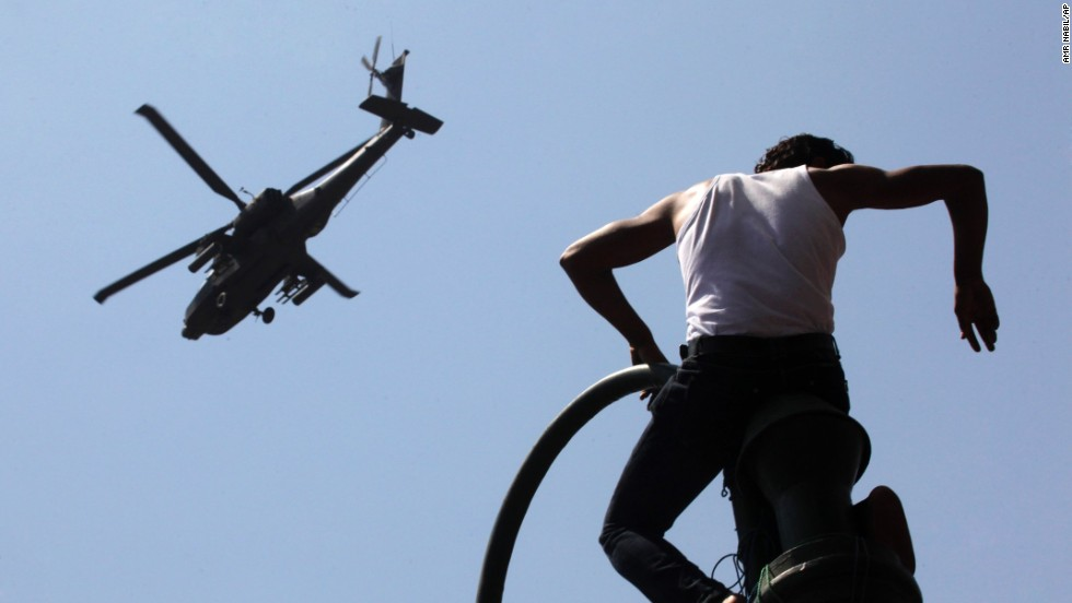 A protester watches an Apache helicopter as it flies over Tahrir Square on June 30. Morsy's opponents stood their ground in the square, where protests two years ago helped topple Hosni Mubarak's 29-year rule.