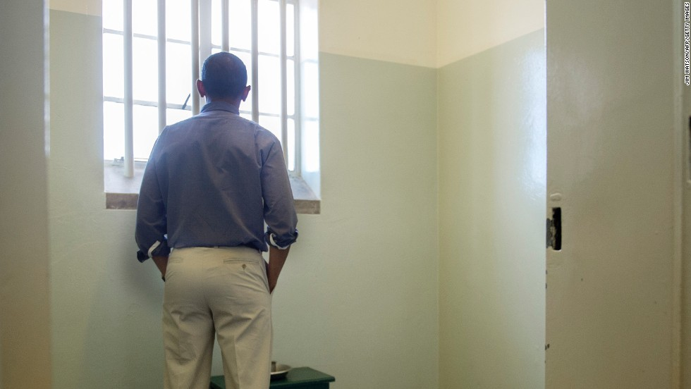 Obama looks out the window of the cell on Robben Island where Nelson Mandela was imprisoned.