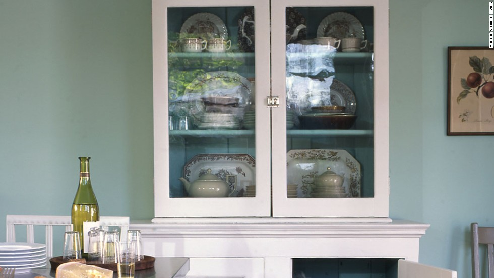 These two flea-market cupboards looked nothing alike, yet it wasn't hard to turn them into a single piece that functions like an armoire. All we did was paint them the same shade of white and blue-green and then add polished-nickel latches and crown molding. We stacked them and placed display items in the glass-front and linens underneath.
