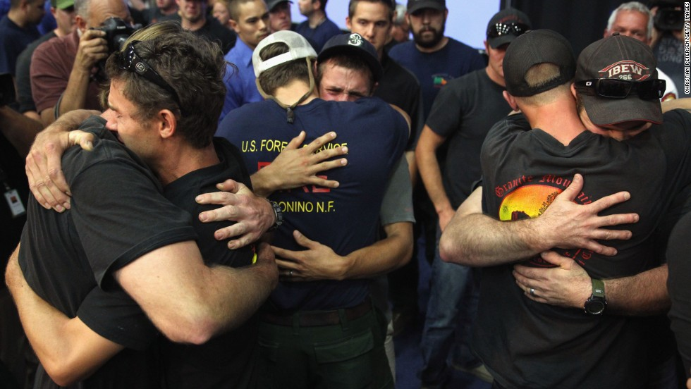 Local firefighters embrace on July 1 at a memorial service in Prescott.