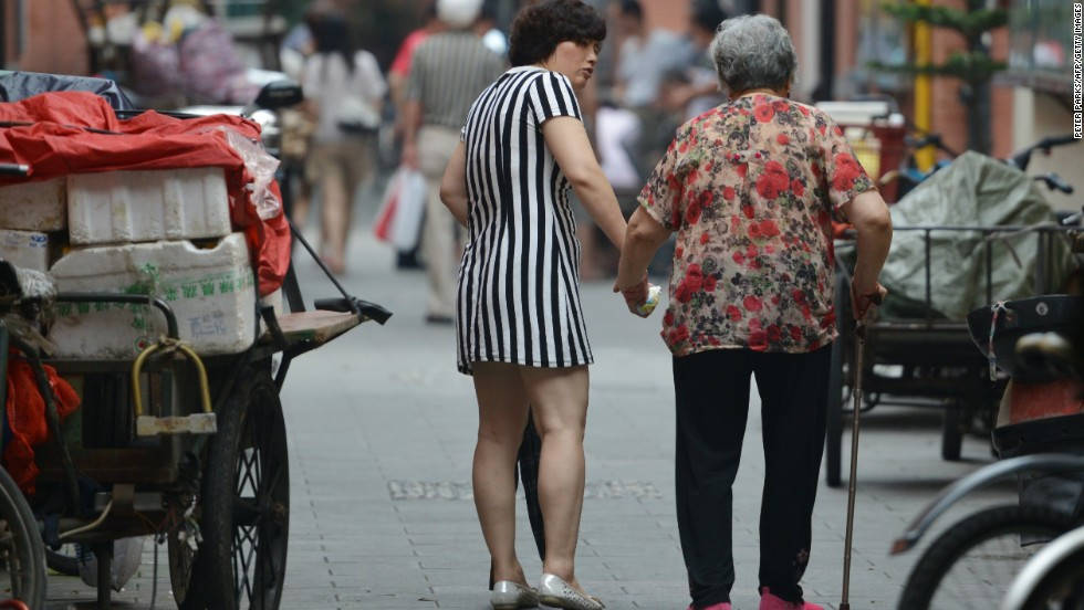 """JULY 2 - SHANGHAI, CHINA: A mother and daughter walk together on July 1. <a href=""""http://cnn.com/2013/07/02/world/asia/china-elderly-law/index.html?hpt=hp_c3""""><br />A new national law</a> introduced this week requires the offspring of parents older than 60 to visit their parents """"frequently"""" and make sure their financial and spiritual needs are met. A third of China's population will be classed as elderly by 2050, <a href=""""http://cnn.com/2013/07/02/world/asia/china-elderly-law/index.html?hpt=hp_c3"""">according to Xinhua.</a>"""