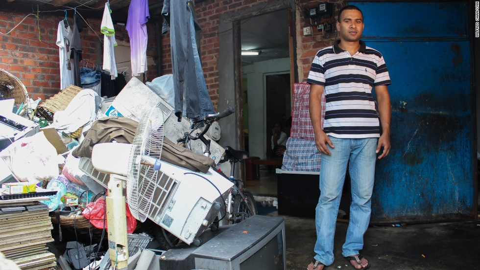 Johir, a refugee from Bangaldesh, stands next to a pile of salvaged objects in the slum village of Ping Che on June 25, 2013. Because asylum seekers are forbidden to make money while awaiting a status determination, Johir must gather clothes and household items from a nearby garbage dump.