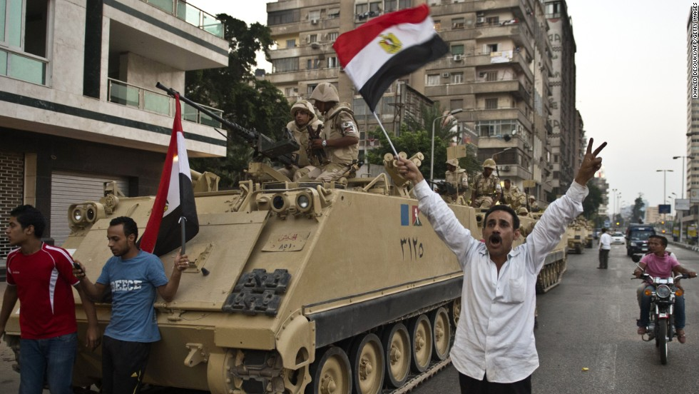 Egyptians salute Army tanks upon their deployment on a street leading to Cairo University on July 3.
