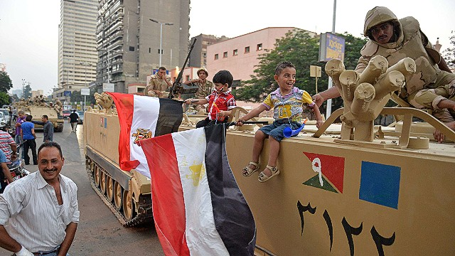 Egyptian children hold national flags as they pose for pictures near army soldiers on an armoured personnel carrier (APC) in a Cairo street on July 3, 2013 after the Egyptian army deployed dozens of armoured vehicles near gathering of Islamist President Mohamed Morsi's supporters. Opposition leader Mohamed ElBaradei and the heads of the Coptic Church and Al-Azhar -- Sunni Islam's highest seat of learning -- will unveil an army roadmap for Egypt's future after President Mohamed Morsi, state television said. AFP PHOTO/KHALED DESOUKIKHALED DESOUKI/AFP/Getty Images