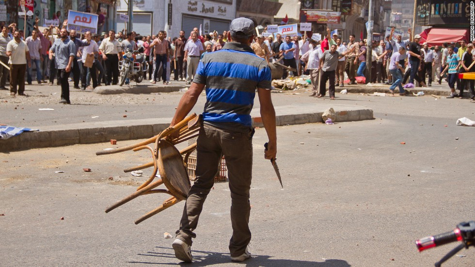 An opposition protester holds a chair and knife during clashes between supporters and opponents of Morsy on July 3 in downtown Damietta, Egypt, which is north of Cairo near the Mediterranean Sea.