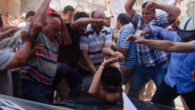 An opposition protester is beaten by pro-Morsy demonstrators during clashes in Damietta on July 3.