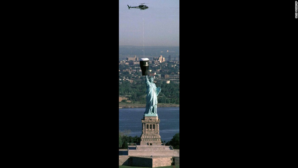 A representation of a giant glass of Guinness is lowered over the Statue of Liberty to publicize the city's first Irish Music & Arts Festival in 1997.
