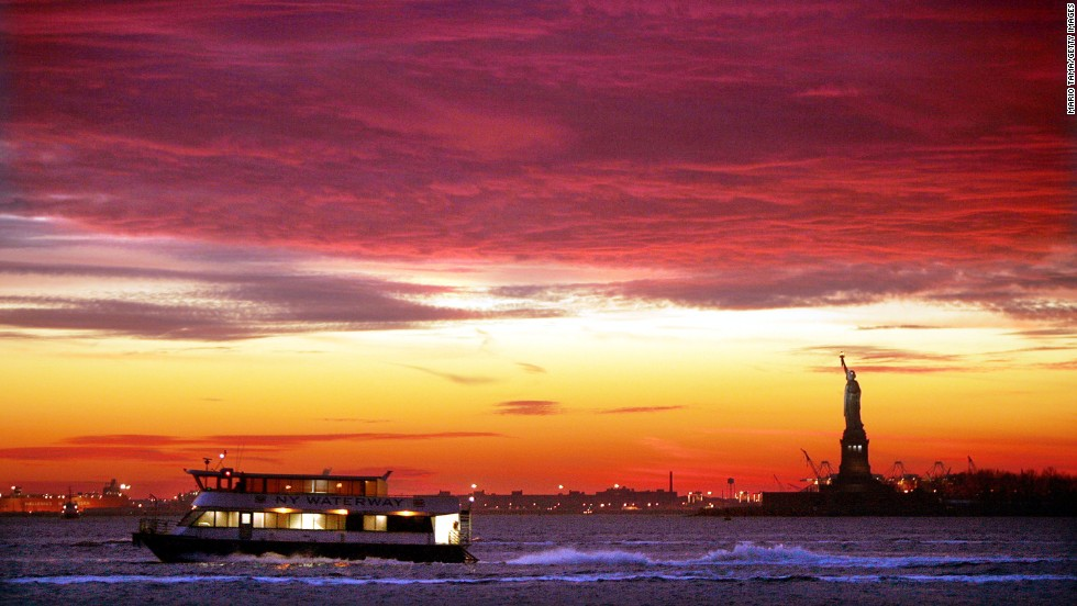 A New York Waterway ferry moves along the water as the sun sets behind the Statue of Liberty in 2004.