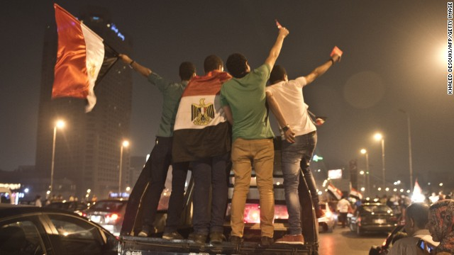 Egyptian youths on police vehicle celebrate in Cairo on July 3, 2013 after a broadcast confirming that the army will temporarily be taking over from the country's first democratically elected president Mohammed Morsi. In their tens of thousands, they cheered, ignited firecrackers and honked horns as soon as the army announced President Mohamed Morsi's rule was over, ending Egypt's worst crisis since its 2011 revolt.