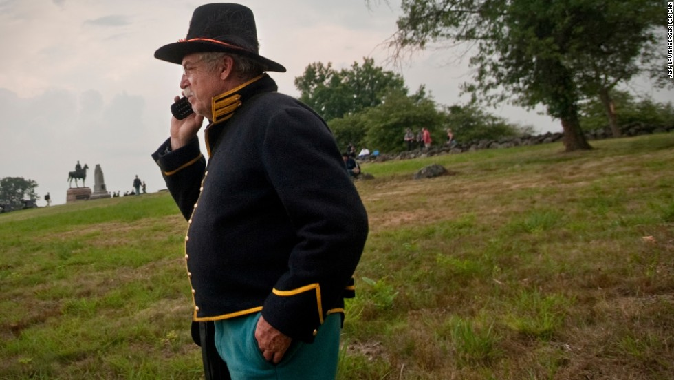 Jim Ranke, a re-enactor from Winchester, Virginia, makes a quick phone call to his son during the National Park Service's opening ceremony on June 30, for the 150th anniversary at Gettysburg National Military Park.