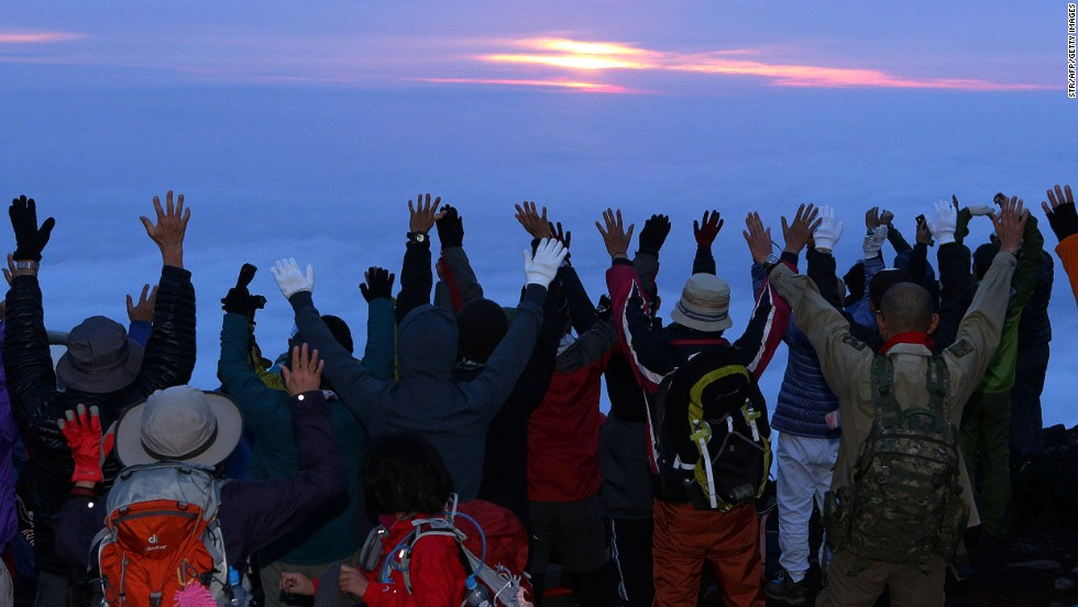Here, climbers who departed at 3 a.m. celebrate their view of the sunrise from Mount Fuji's summit.