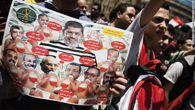 A celebrant bears a  poster on July 4 showing Mohamed Morsy surrounded by leading Muslim Brotherhood figures as babies.