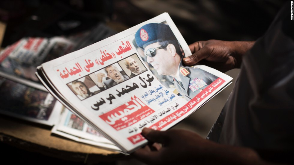 A man holds a newspaper near Mesaha Square in Cairo on July 4.