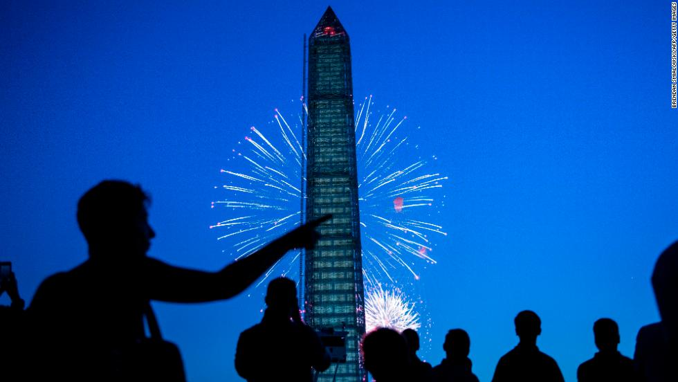 People watch fireworks burst behind the Washington Monument on the National Mall in Washington on Thursday, July 4. People across the United States gathered on Thursday to celebrate Independence Day with parades, picnics and fireworks.