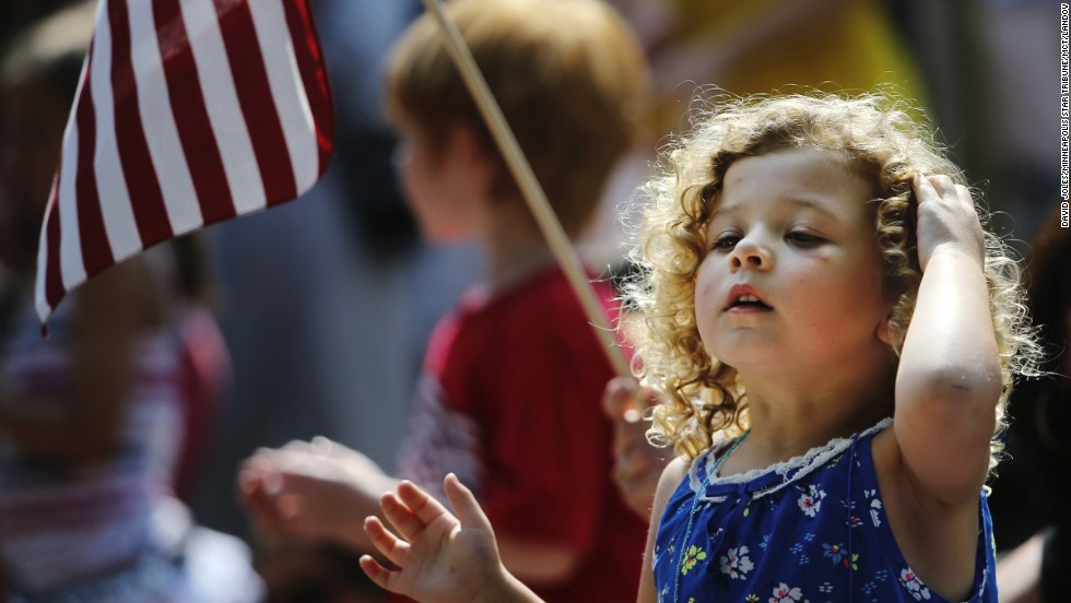 Meriya Merrill, 3, cranes her neck to take in the Independence Day parade in Edina, Minnesota, as her grandmother holds a flag behind her.