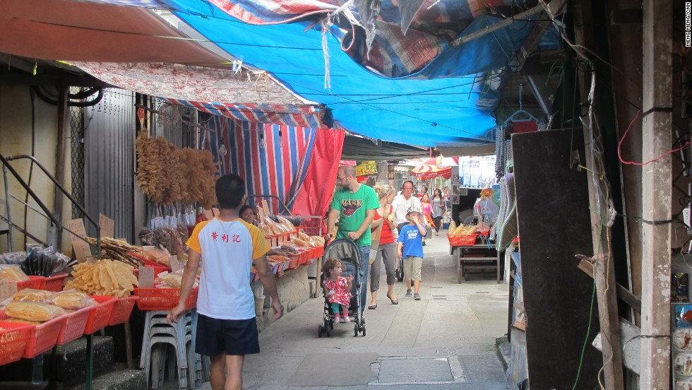 Tourists walk down Tai O's main street, where locals operates seafood stores and souvenir shops.