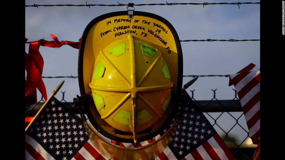 A firefighter's helmet from a Texas volunteer department hangs on a fence at a makeshift memorial to the fallen Granite Mountain Hotshots in Prescott on July 4.