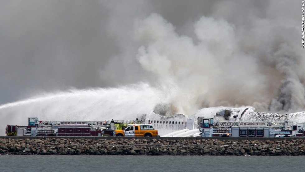 Fire crews work at the crash site at San Francisco International Airport on July 6.