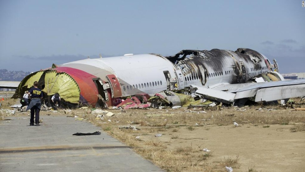 "An investigator stands near the tail of the plane in a handout photo released on July 7. The NTSB has ruled out weather as a problem and said that conditions were right for a ""visual landing."""