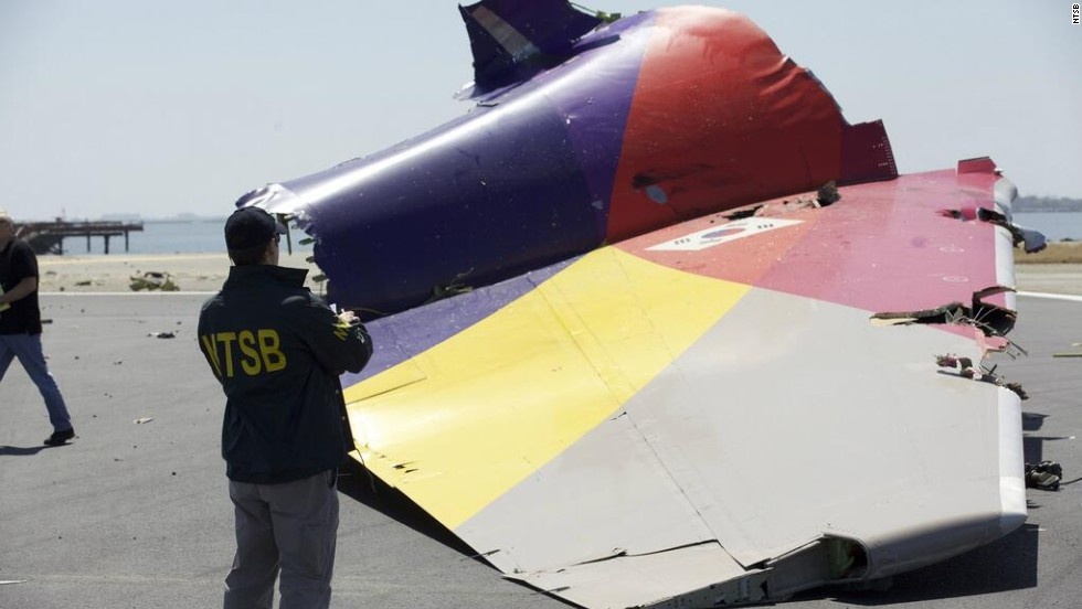 An investigator inspects the broken-off tail of the plane in a handout photo released July 7. The crash killed two people, injured 182 and forced the temporary closure of one of the country's largest airports.