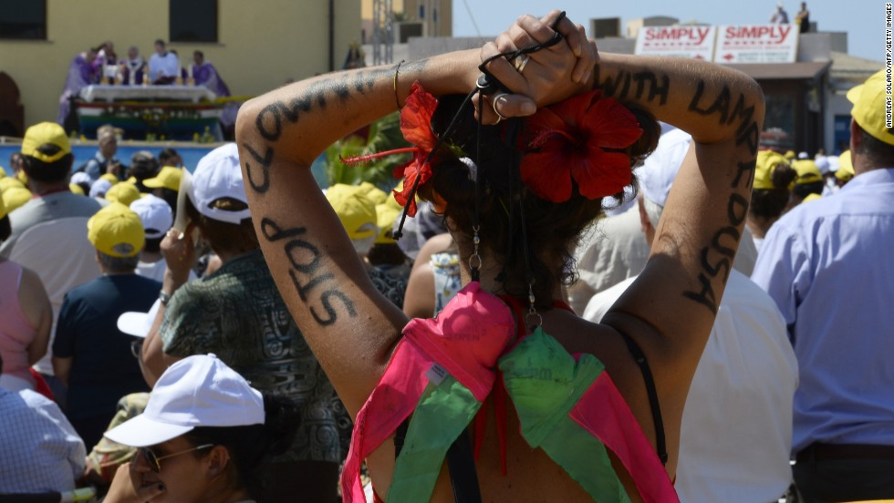"A faithful has ""Stop clowning with Lampedusa"" painted on her arms as the pope led  the mass. ""The culture of well-being, that makes us think of ourselves, that makes us insensitive to the cries of others, that makes us live in soap bubbles, that are beautiful but are nothing, are illusions of futility, of the transient, that brings indifference to others, that brings even the globalization of indifference,"" said Pope Francis. <br />"