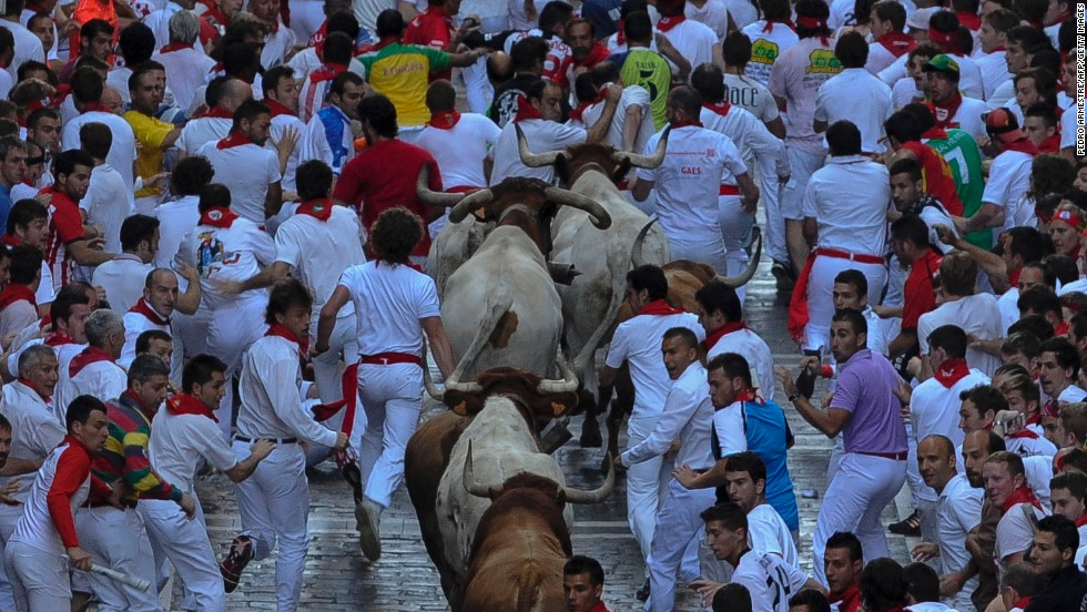 At 8 a.m. sharp, rockets are fired to signal the start of the Bull Run. Six fighting bulls are released from their pen. Humans and bulls then begin a mad race through the cobbled streets of Pamplona, ending up in the central bull ring.