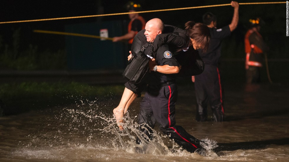 A police officer carries away a woman from the partially submerged commuter train on July 8.