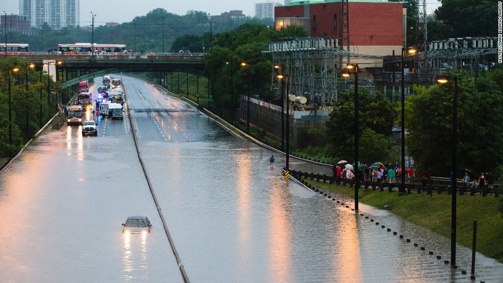 Heavy storms cause power outages and flooding across Toronto on Monday, July 8. Here, a driver on the Don Valley Parkway becomes stuck in floodwaters. Toronto's main north-south artery was closed in both directions overnight, with stranded motorists forced to abandon their vehicles.