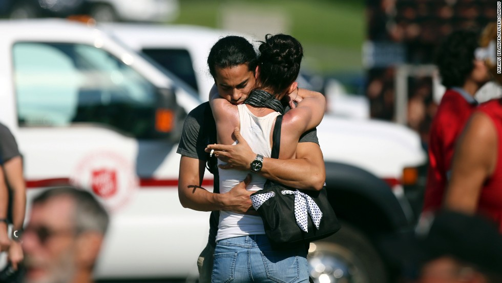 A man consoles a woman on July 8 at the Polyvalente Montignac, the school used as a shelter for evacuated Lac-Megantic residents.
