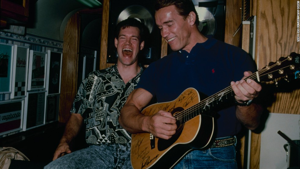 Travis laughs with Arnold Schwarzenegger in 1990.