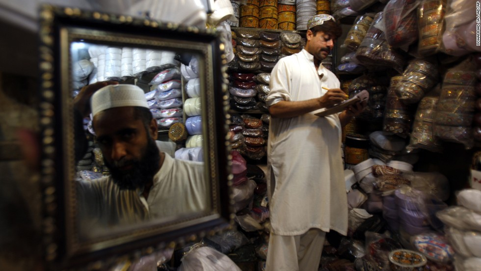 A customer tries on a cap ahead of Ramadan, in Peshawar, Pakistan, on July 9.