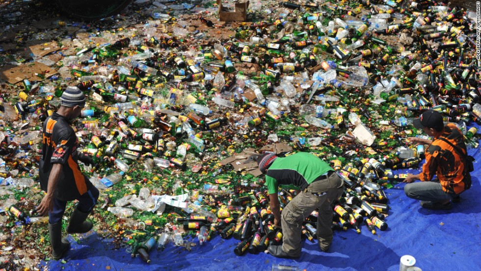Police destroy hundreds of bottles of alcohol and pirated DVDs seized during recent raids as they prepare for Ramadan in a Jakarta police station on July 8.