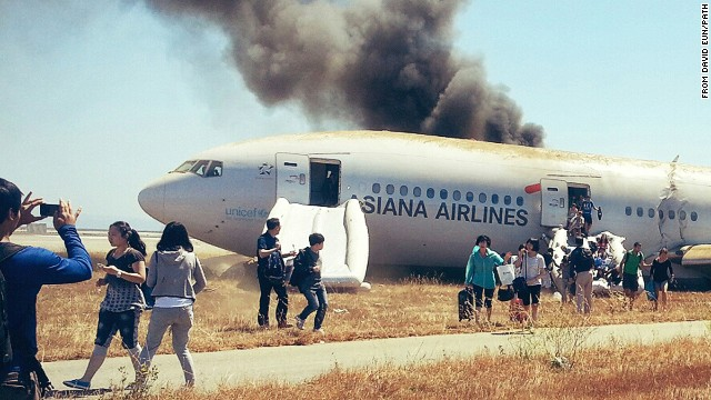 Several passengers escape Asiana Airlines flight 214 with their baggage and stop to take photos of the burning wreckage.