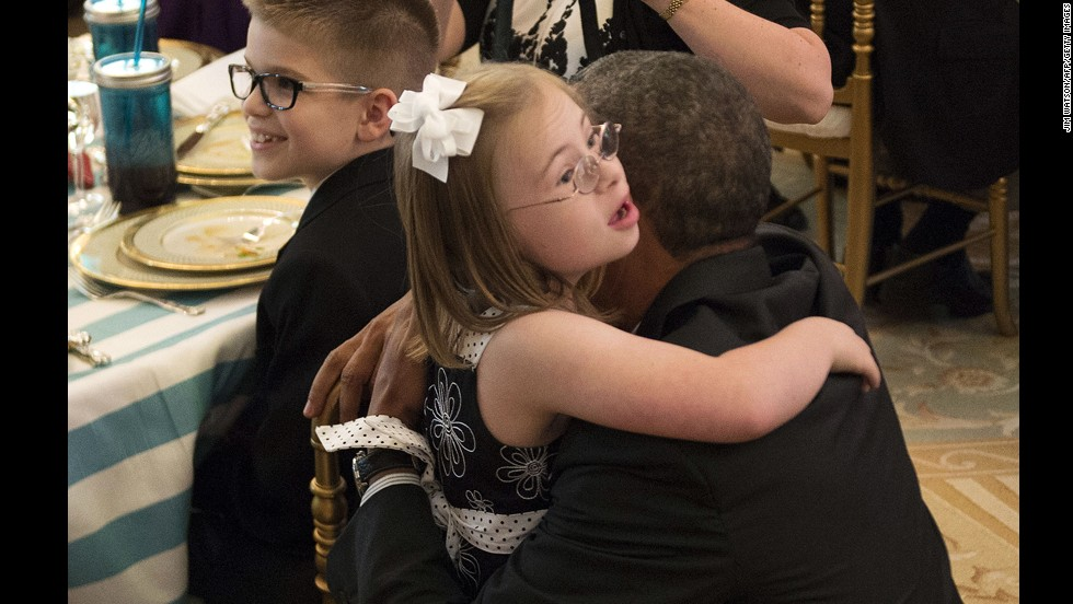 Makenna Hurd, 9, from Mascot, Tennessee, gives President Obama a hug during the dinner. Hurd won for her Bodacious Banana Muffins recipe.