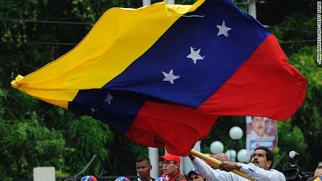 Venezuelan acting president Nicolas Maduro (C) flutters a Venezuelan national flag during the opening rally of his campaign in Barinas, Venezuela on April 2, 2013. Venezuelans will elect new president next April 14. AFP PHOTO/JUAN BARRETO (Photo credit should read JUAN BARRETO/AFP/Getty Images)