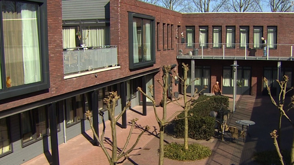 The two-story buildings form a courtyard where residents can roam on their own and where they are watched by carers, some of whom staff the site's shops.