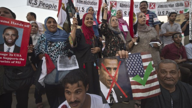 Egyptians in Tahrir Square hold posters and banners on Sunday expressing love of Americans and dislike of President Obama.