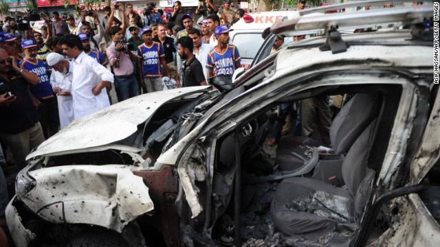 Pakistani security officials gather beside the wreckage of a vehicle at the site of the bomb blast in Karachi on Wednesday.