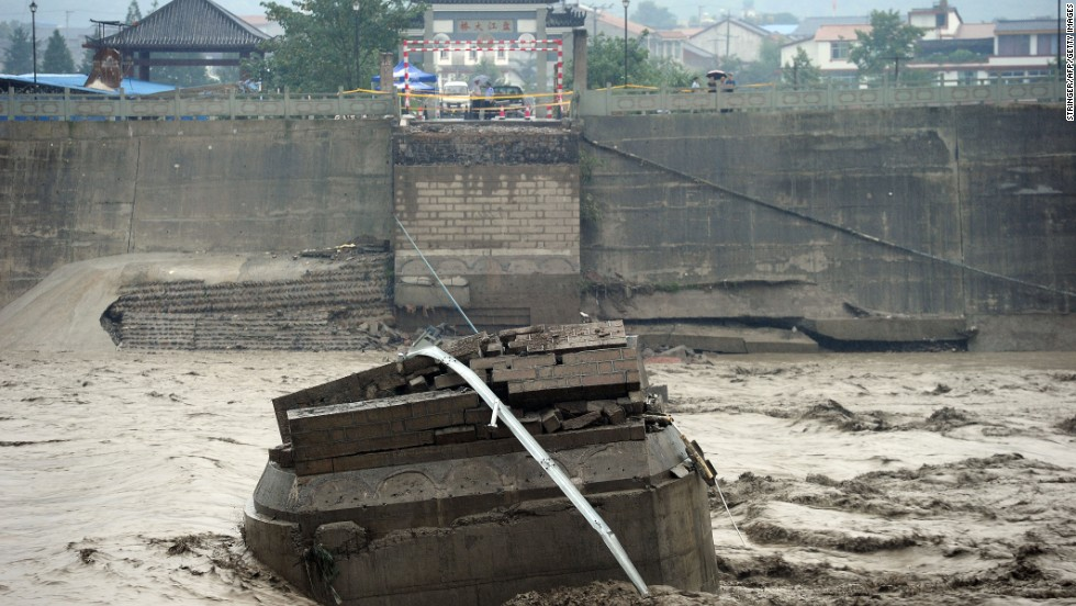 The ruins of the collapsed Panjiang Bridge, also called Qinglian Bridge, lie in a flooded river in the city of Jiangyou on July 9.