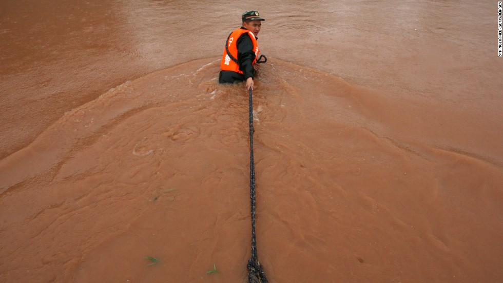 A rescuer pulls a ship in a flooded area of Suining city on Monday, July 1.