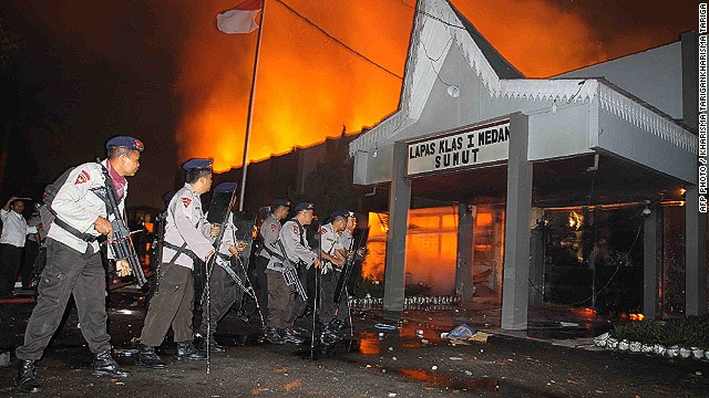 Armed Indonesian police secure the entrance of a burning prison compound in Medan city on July 11, 2013.