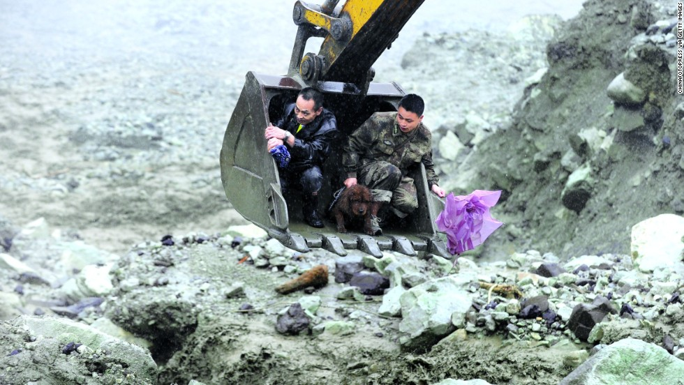 Rescuers evacuate residents with an excavator on Wednesday, July 10, after a landslide hit Wenchuan, China. Flooding that triggered the landslide reportedly has affected 1.5 million people.