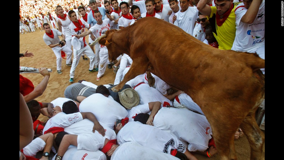 A bull jumps over revelers in the ring at the end of the fifth run on July 11.