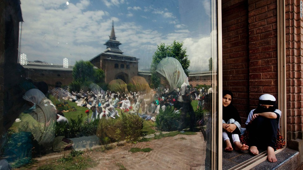 Men are reflected in glass as women pray inside the Jamia Masjid, or Grand Mosque, in Srinagar, India, on July 12.