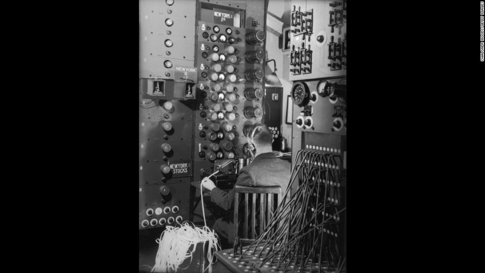 A telegram operator receives a ticker tape message at a Cable & Wireless office circa 1938.