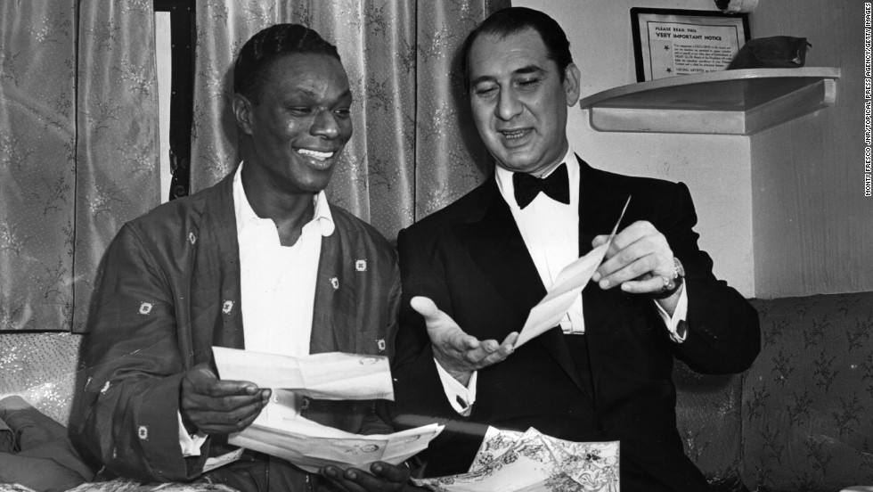 March 23, 1954: American singer Nat King Cole (1919 - 1965) reads congratulatory telegrams with comedian Henny Youngman after the success of their debut at the London Palladium.