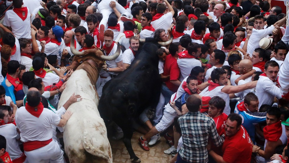 Runners trip and fall ahead of the bulls blocking the entrance to the bull ring on July 13.