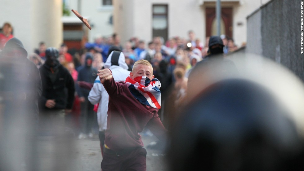 A man throws debris at police on July 13. The parade route was decided by the Northern Ireland Parades Commission, which works to keep friction between the two factions at a minimum.